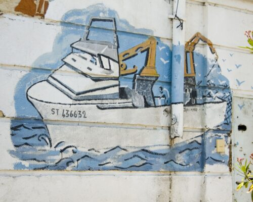 Mural of fishing boat on wall by our quaside restaurant, Les Demoiselles Dupuy, Ste